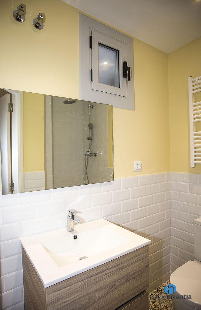 Cuarto de baño con paredes amarillas en calle València de Barcelona