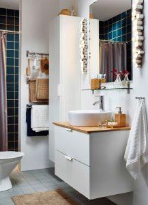 Cuarto de baño con mueble de almacenaje en el lavabo.